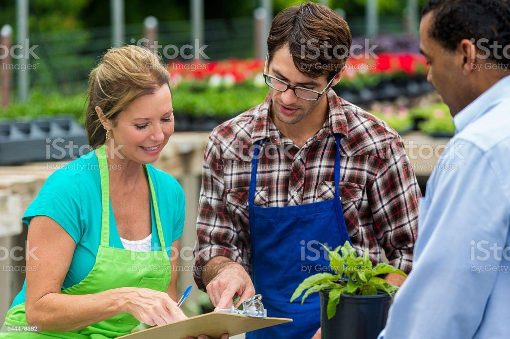 Happy garden center employees looking at paperwork in the garden stock photo