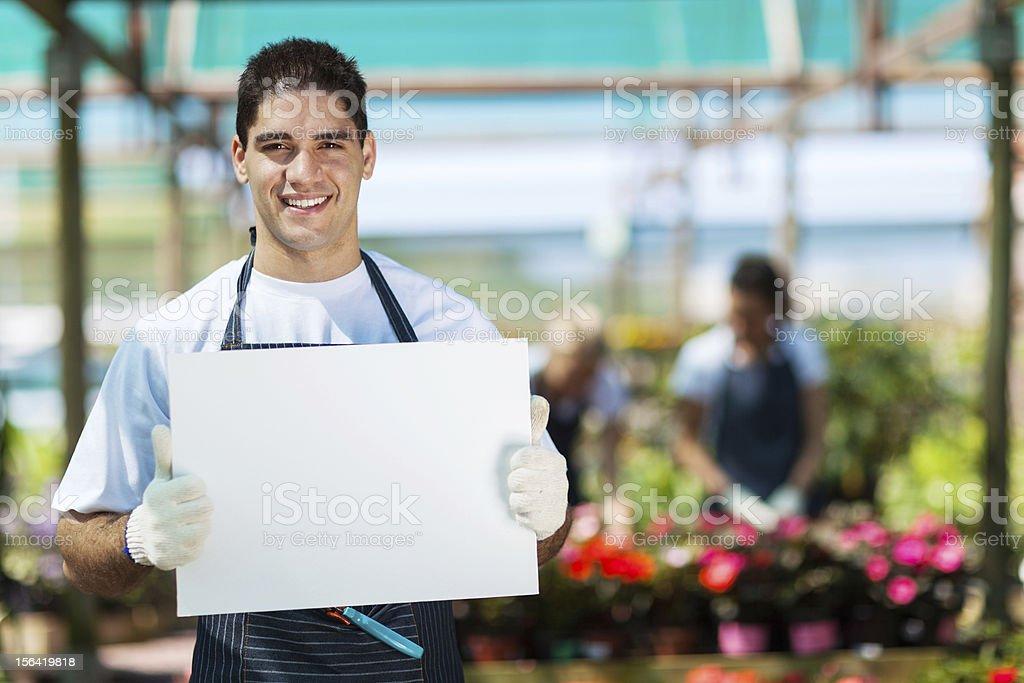 happy gardener holding white board royalty-free stock photo