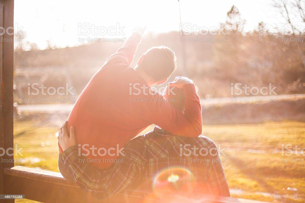 happy gay couple watching sunset stock photo