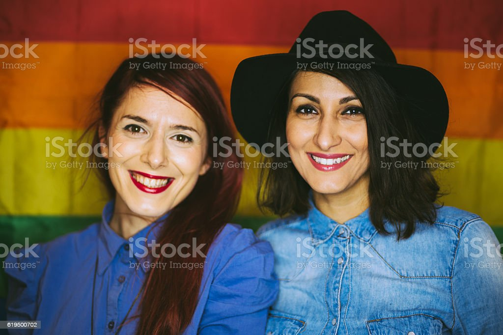 Happy Gay Female Couple on Gay Flag Background. stock photo
