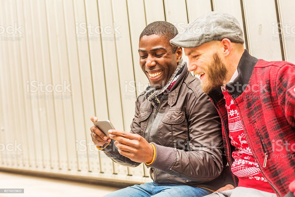 Happy Gay Men Couple Looking at a Mobile Smart Phone stock photo