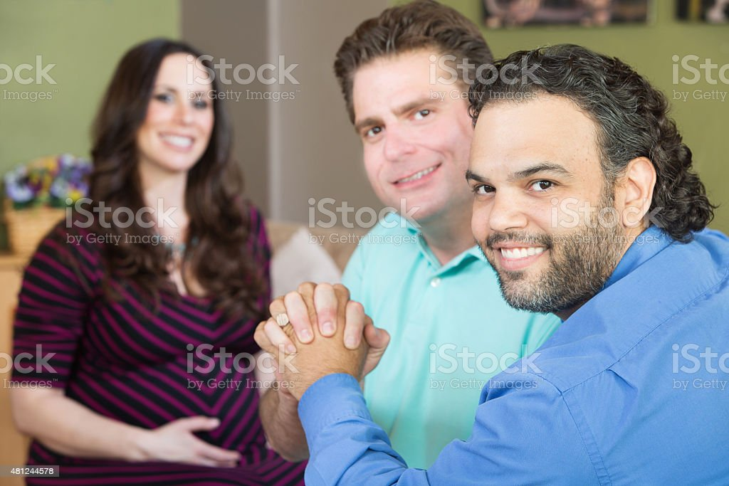 Happy Gay Parents with Pregnant Woman stock photo