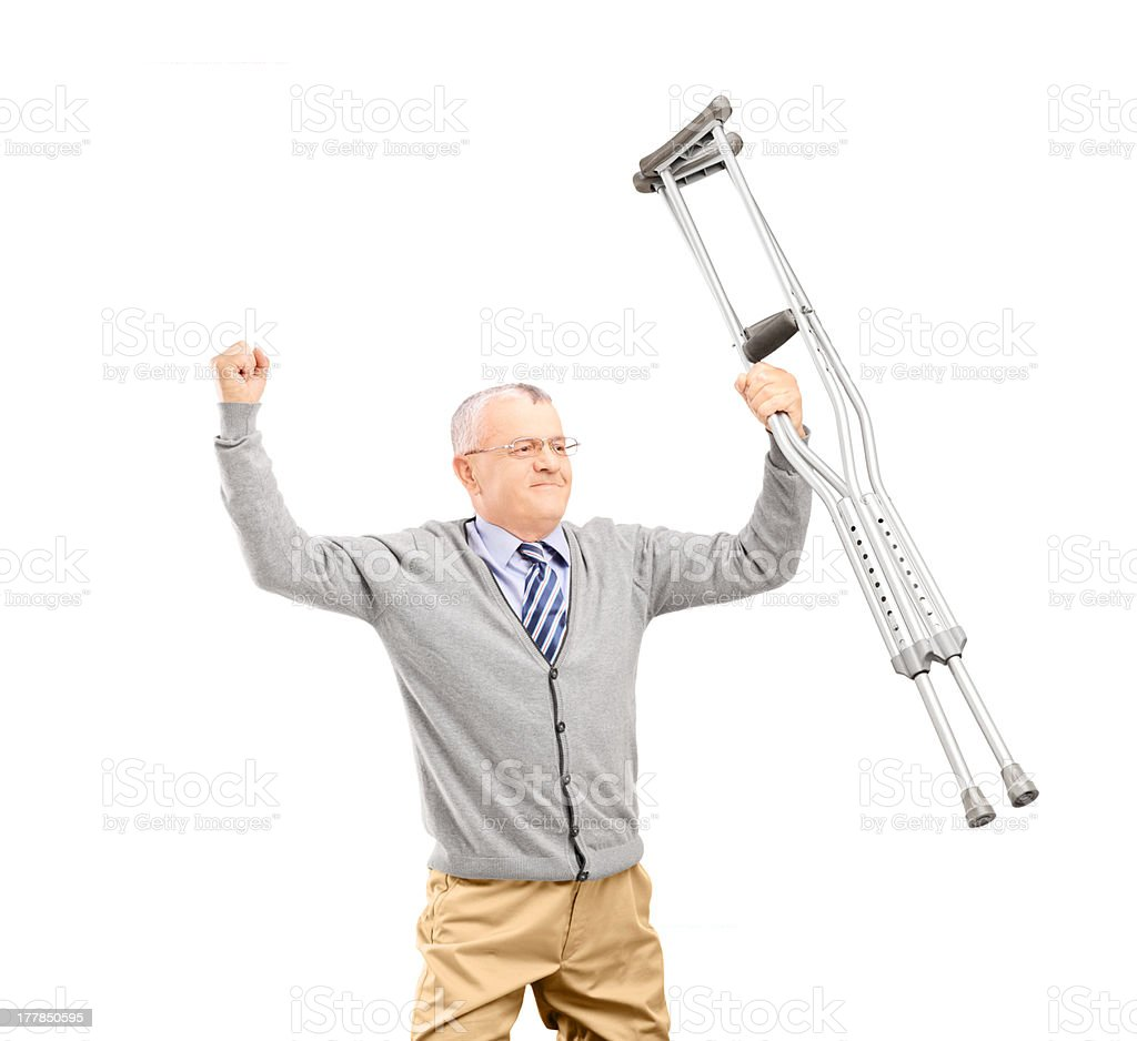 Happy gentleman patient holding crutches and gesturing happiness royalty-free stock photo