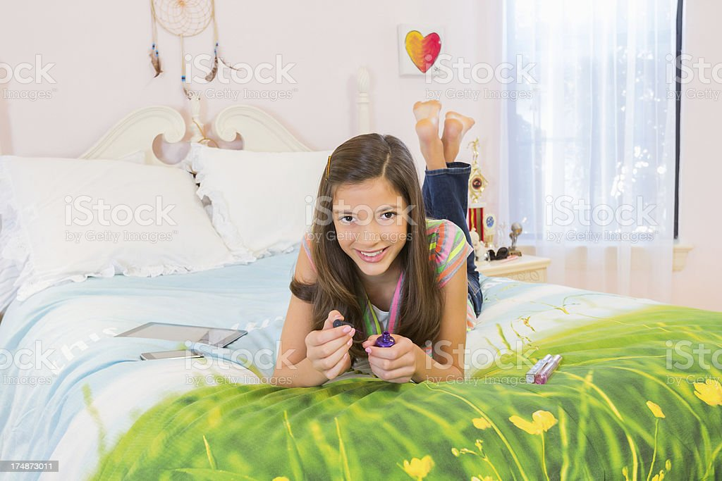 Happy Girl Applying Nail Polish In Bed royalty-free stock photo