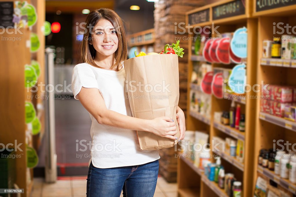 Happy girl buying food at the supermarket stock photo