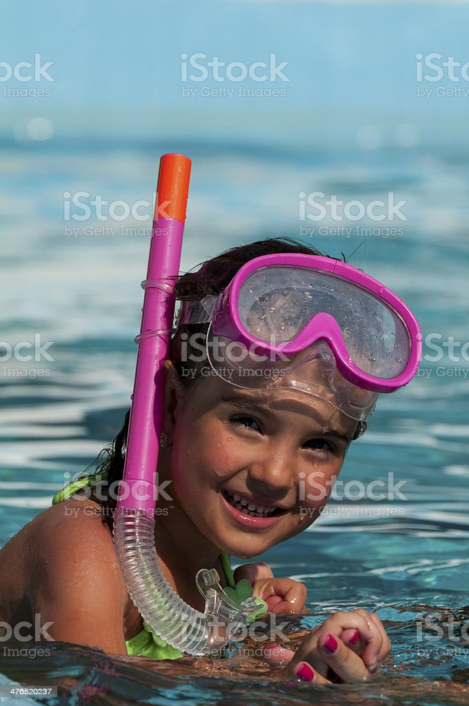Happy Girl Child In Swimming Pool with Goggles and Snorkel stock photo