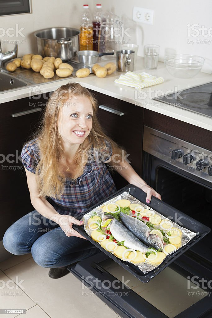 Happy girl cooking raw fish in oven royalty-free stock photo