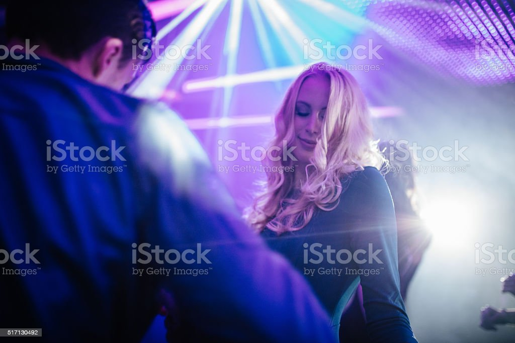 Happy girl dancing and flirting with boy in a club stock photo