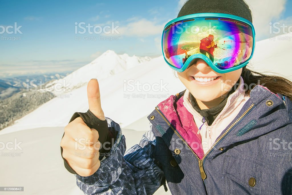 Happy girl dressed in ski or snowboard fashion mask goggles stock photo