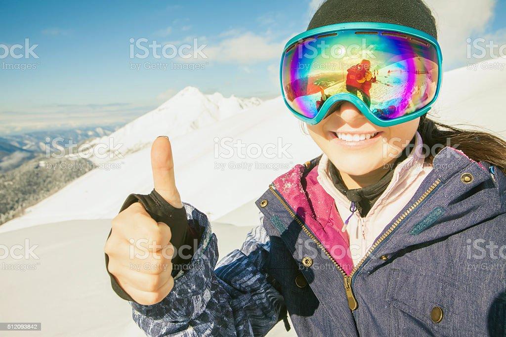 Happy girl dressed in ski or snowboard fashion mask goggles stock photo