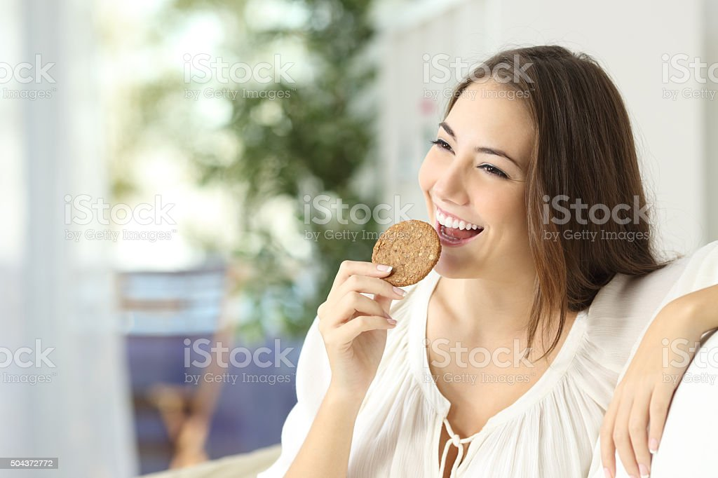Happy girl eating a dietetic cookie stock photo