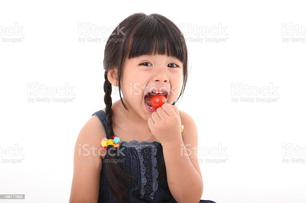 Happy girl eating fresh cherry tomato stock photo
