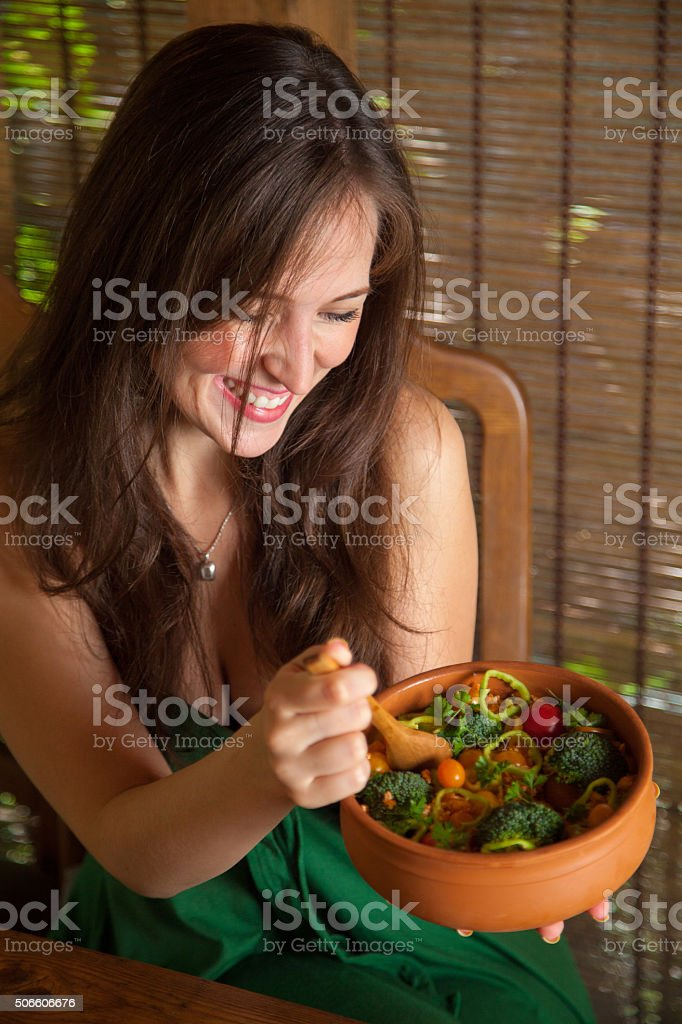 Happy girl eating vegan quinoa salad. stock photo