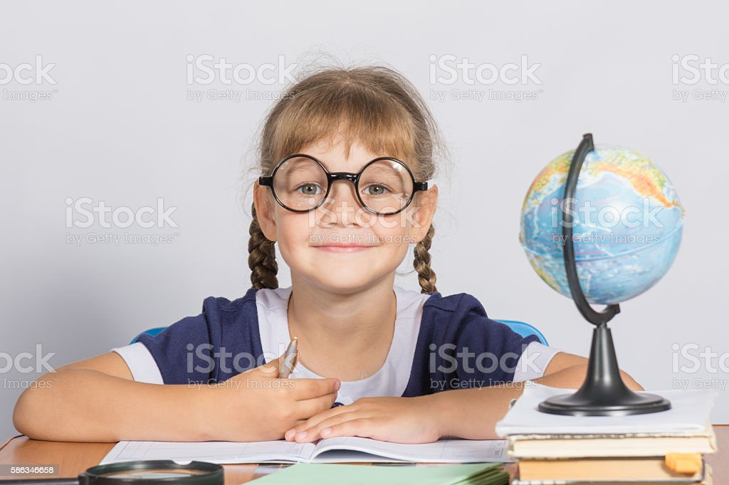 Happy girl first grader sits at a table stock photo