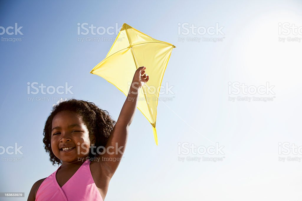 Happy girl flying a kite stock photo
