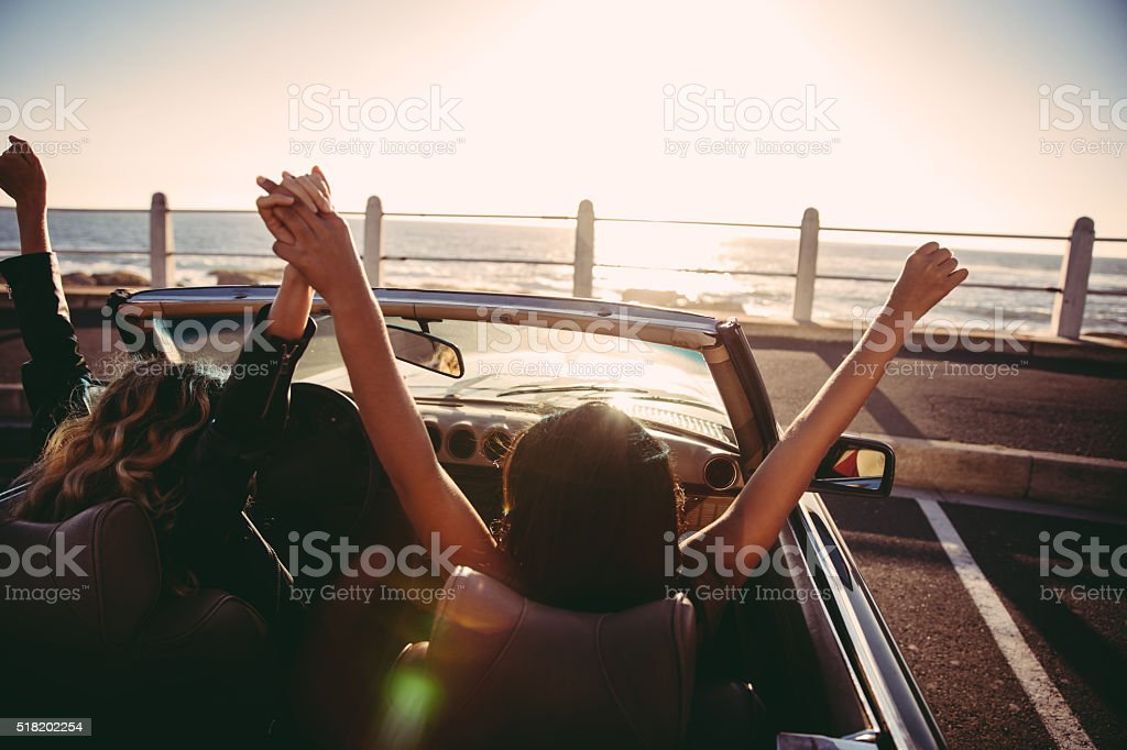 Happy girl friends cheering with raised arms in a convertible stock photo