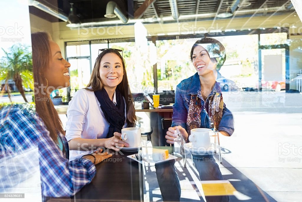 Happy girl friends having lunch together in coffee shop stock photo