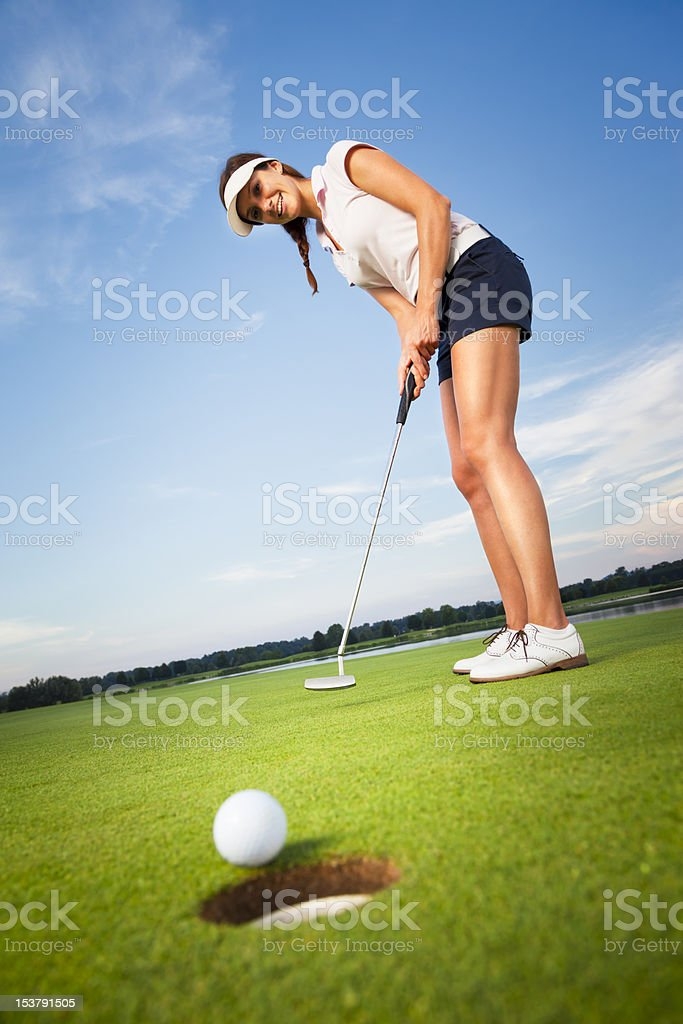 Happy girl golfer putting ball into hole. royalty-free stock photo