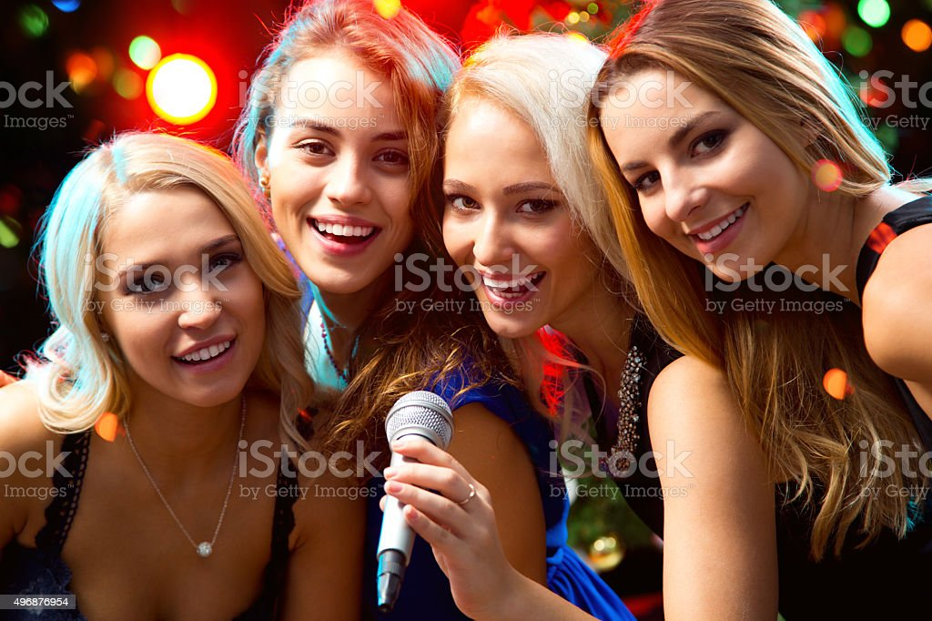 Happy girl having fun singing at a party stock photo