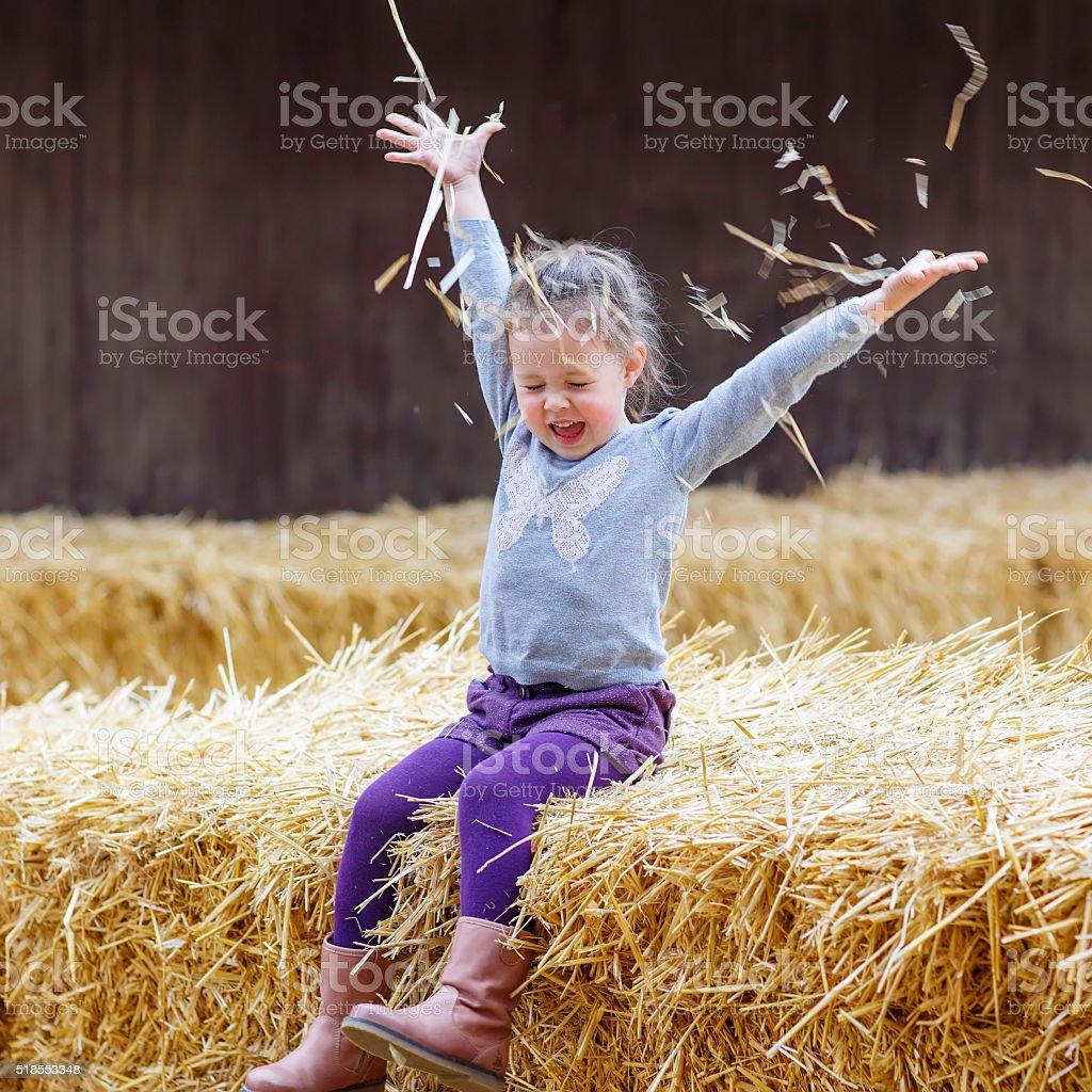 happy girl having fun with hay on a farm stock photo