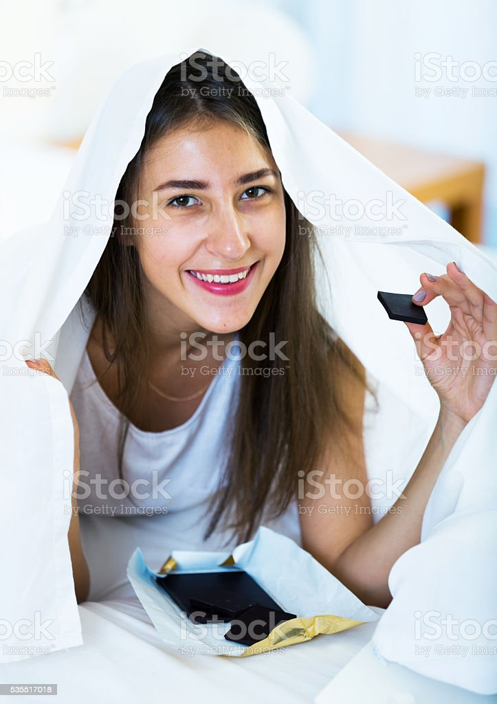 Happy girl hiding under sheet with sweets indoors stock photo