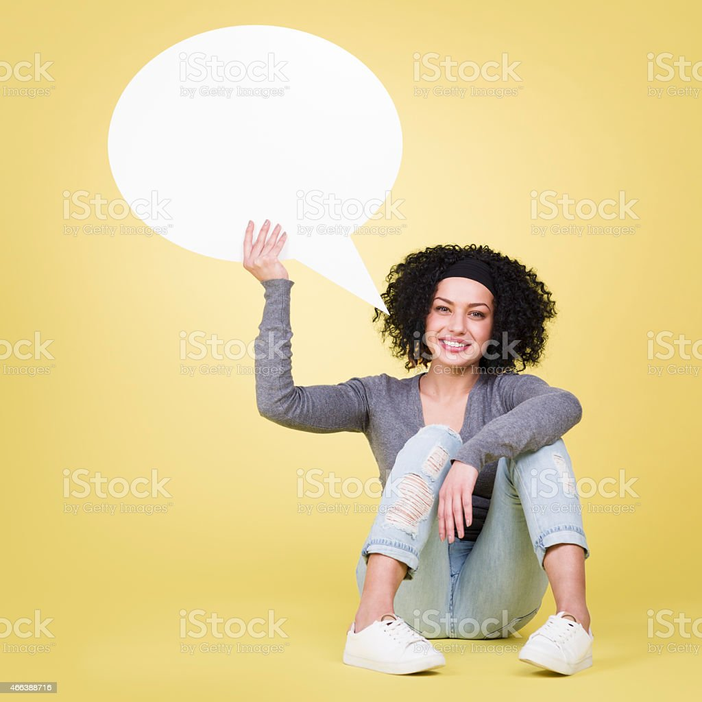 Happy girl holding a blank speech balloon with copy space. stock photo