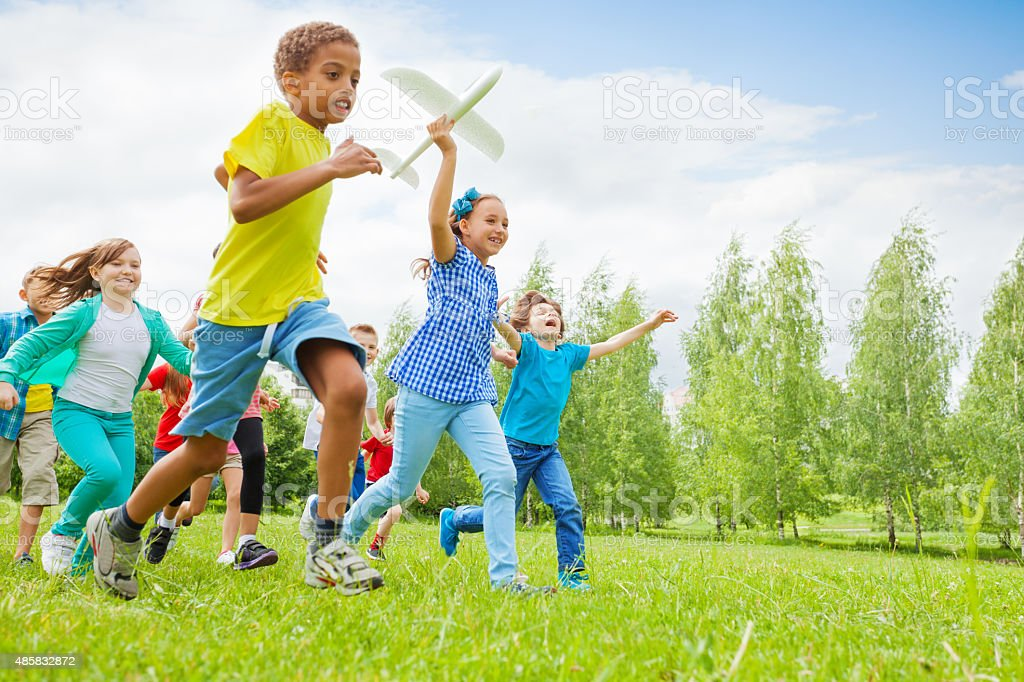 Happy girl holding airplane toy and children near stock photo