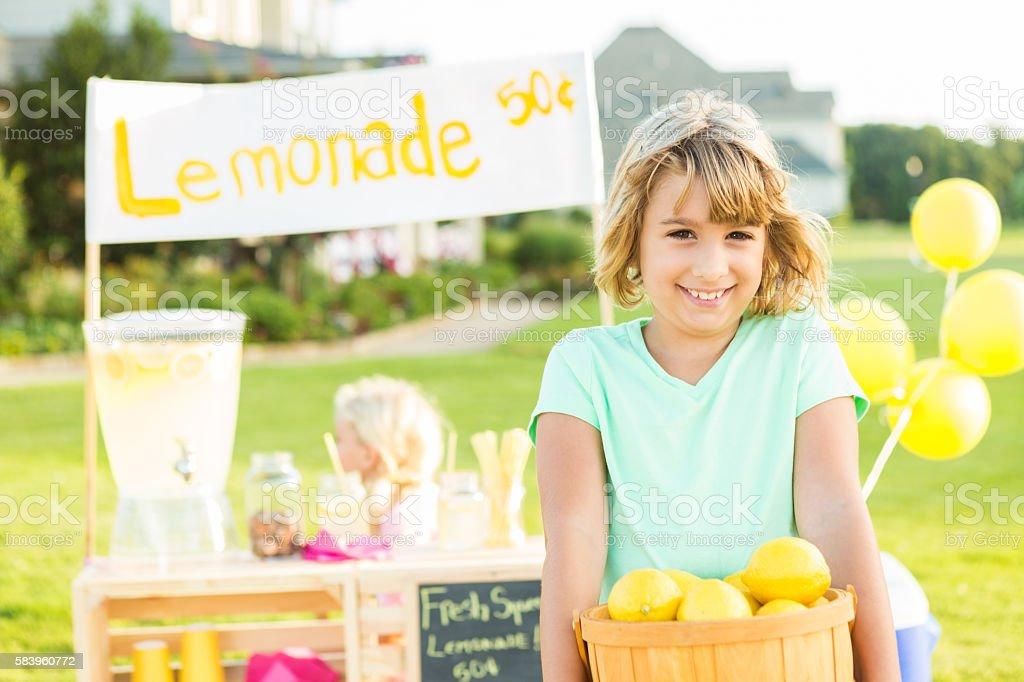 Happy girl holding basket of lemons at her lemonade stand stock photo