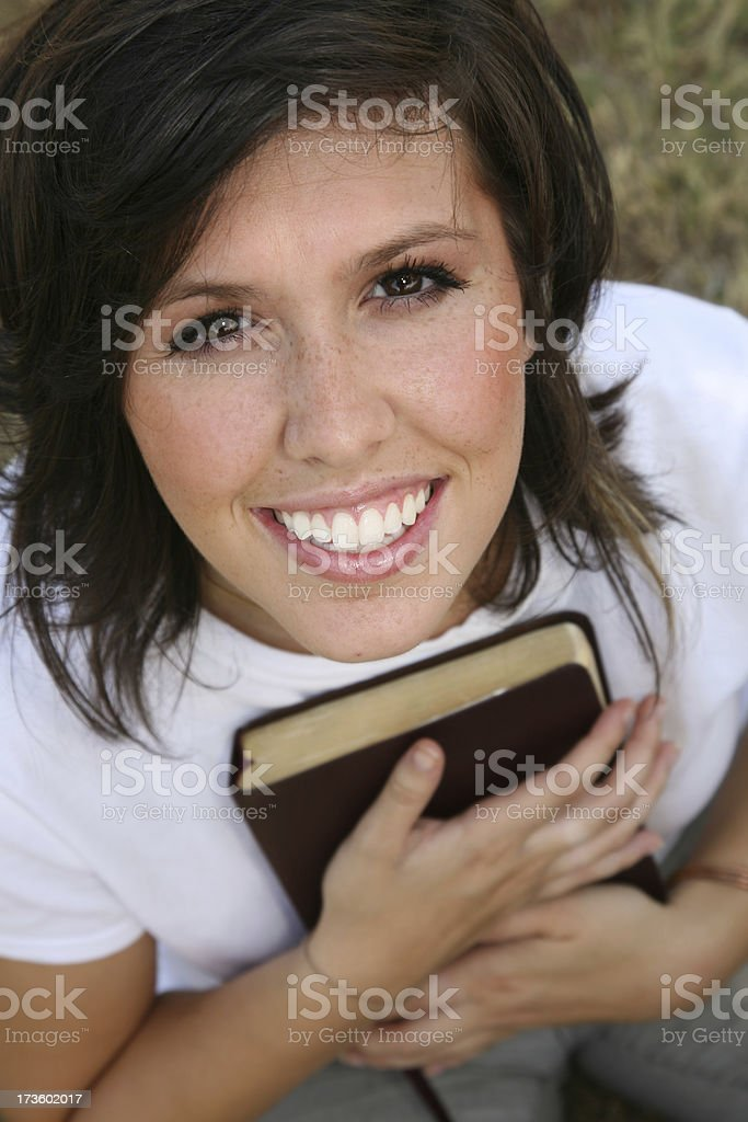 Happy Girl Holding Bible Close To Her heart royalty-free stock photo