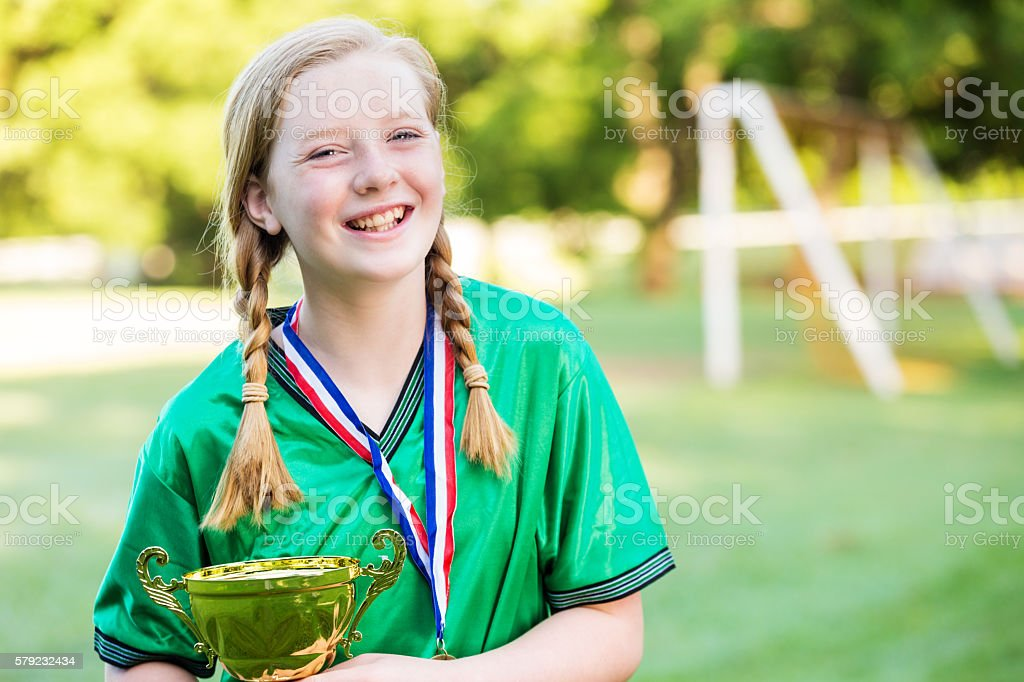 Happy girl holding her trophy after winning the soccer game stock photo