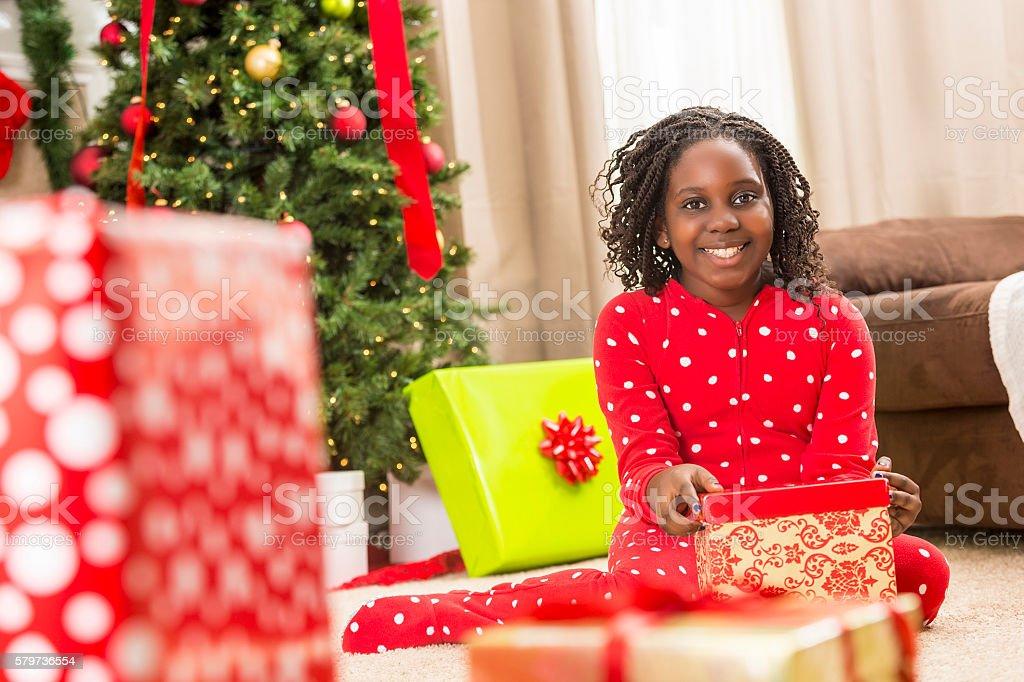 Happy girl in red onesie pajamas opening Christmas presents stock photo