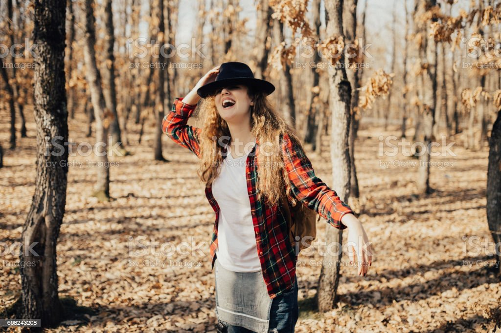 Happy girl in the woods covering her head with a hat stock photo