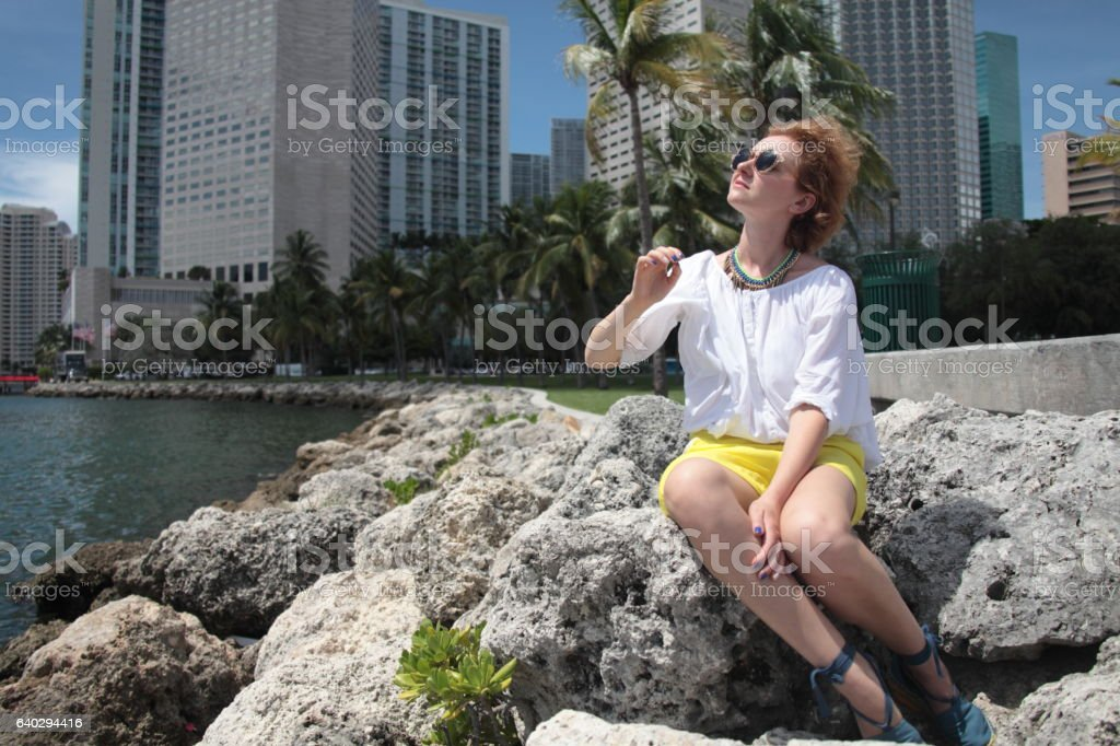 happy girl is sitting on a stones. stock photo