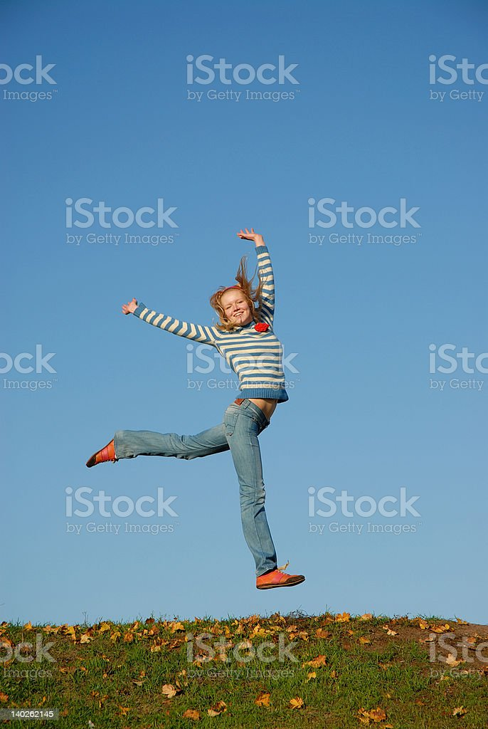 Happy girl jumping against the blue sky royalty-free stock photo