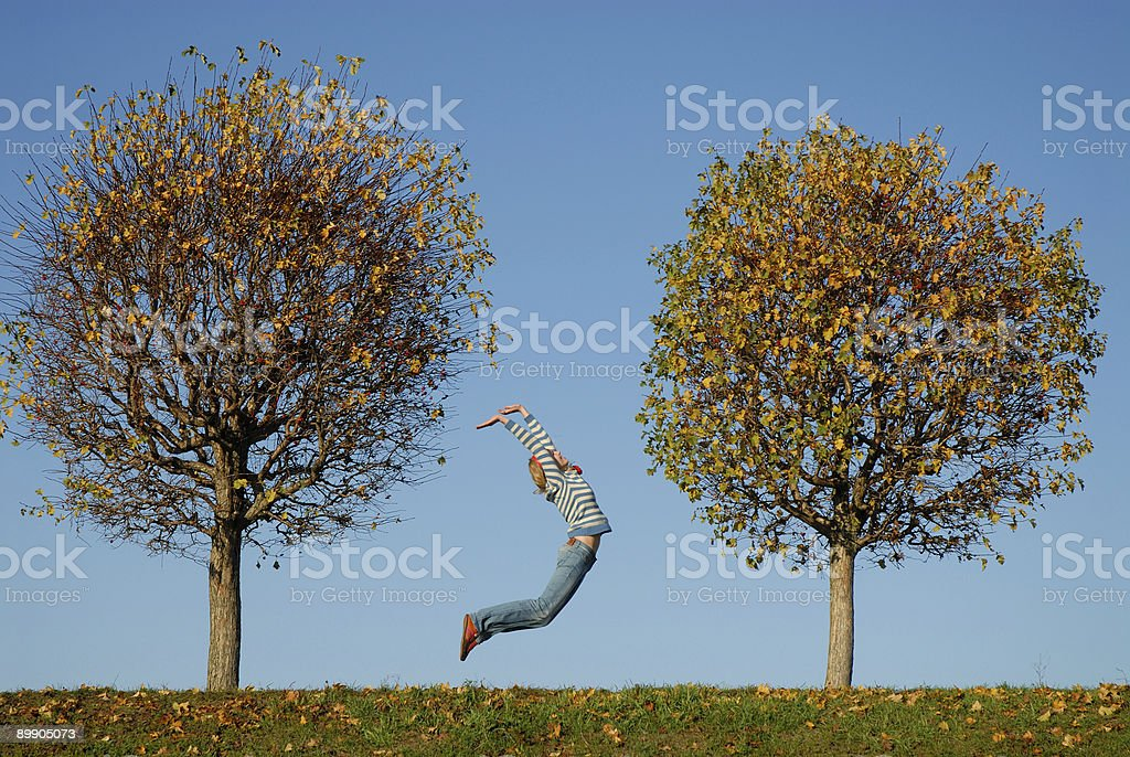 Happy girl jumping between two trees royalty-free stock photo