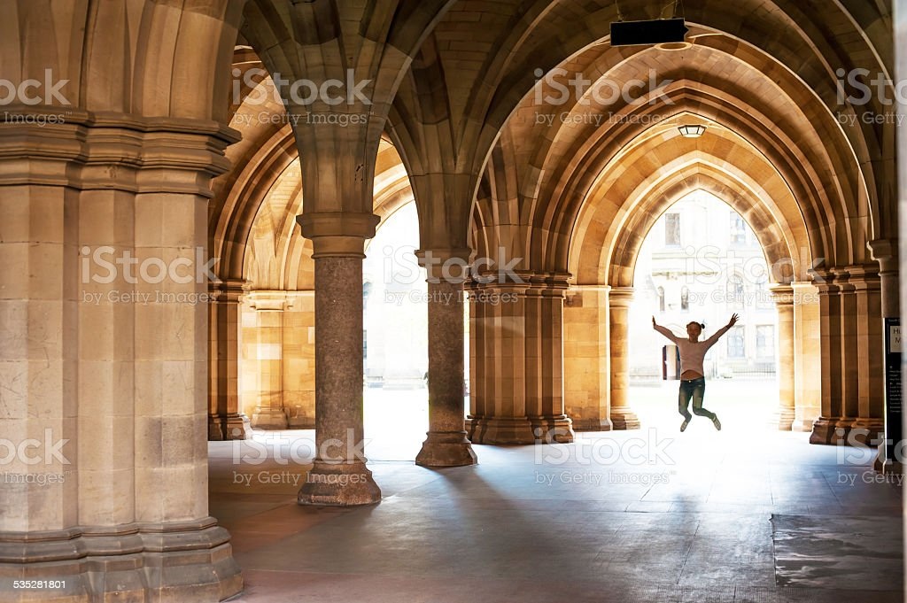 Happy girl jumping high up in cloisters of Glasgow University. stock photo
