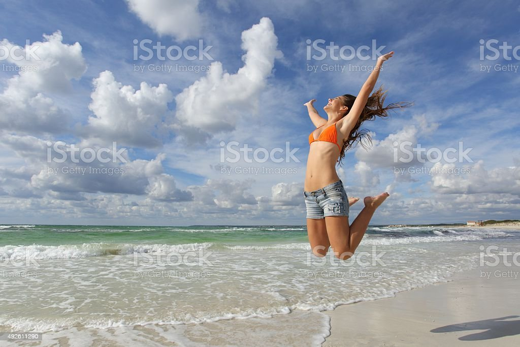 Happy girl jumping on the beach on holidays stock photo