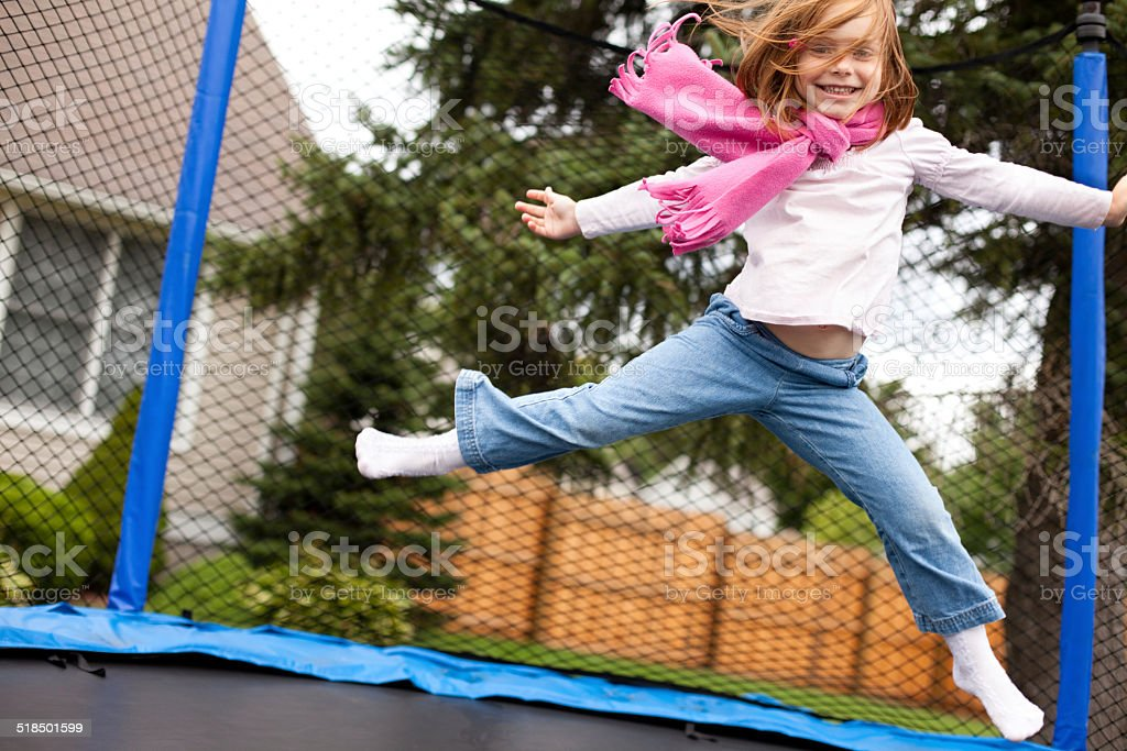 Happy Girl Jumping Outdoors on Trampoline stock photo