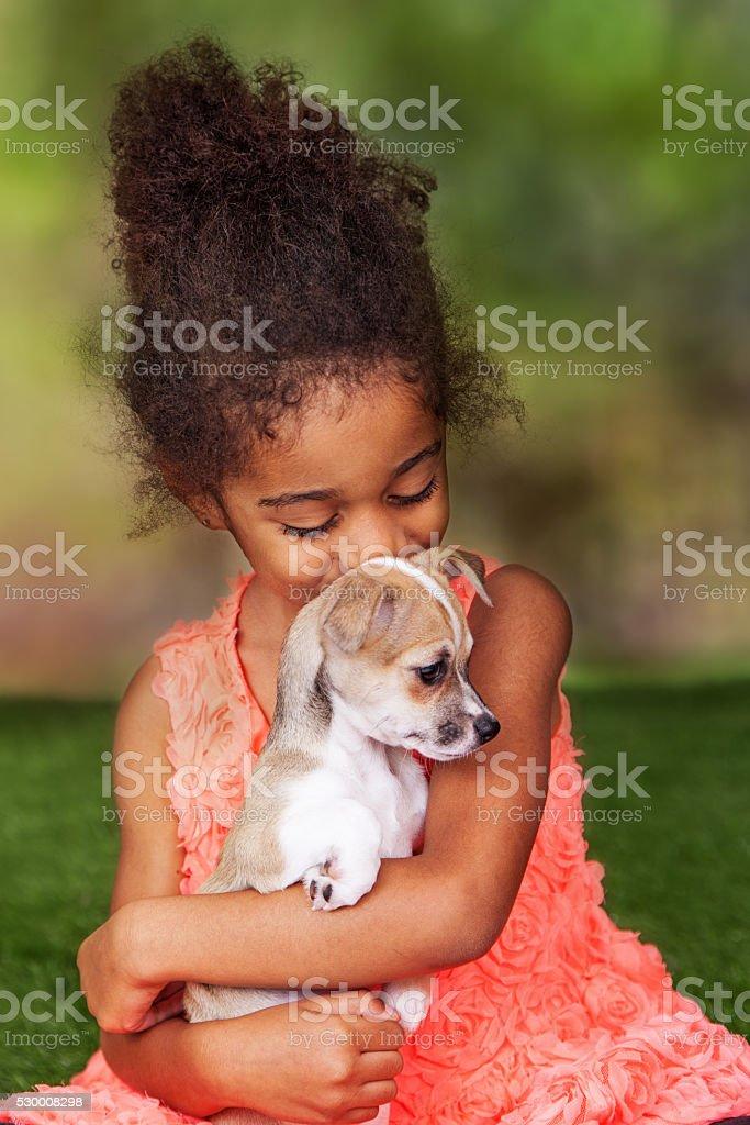 Happy Girl Kissing Puppy stock photo