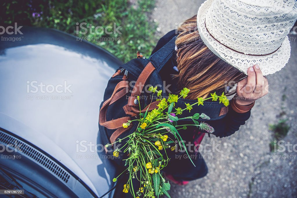 Happy girl leaning on a car stock photo