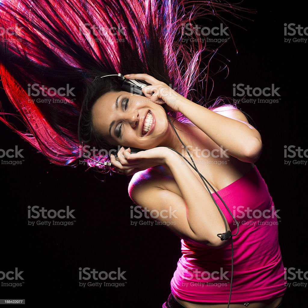 Happy girl listening music with Headphones on black background stock photo