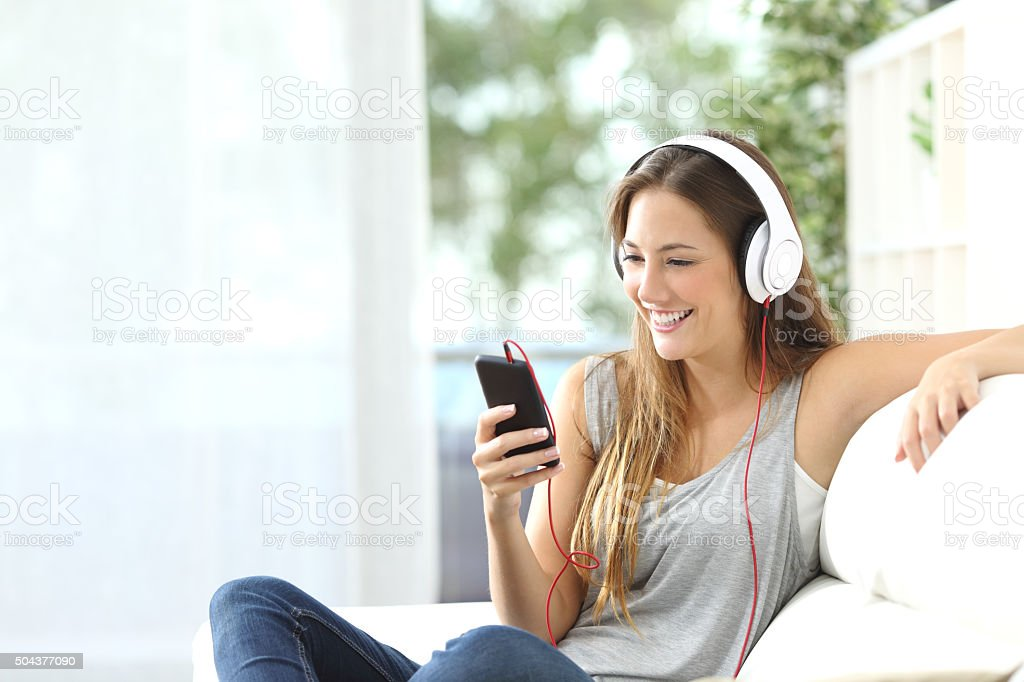 Happy girl listening to music from mobile phone stock photo