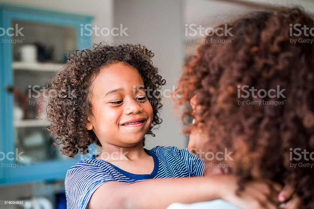 Happy girl looking at mother at home stock photo