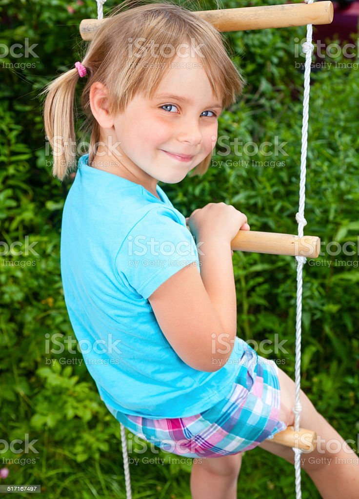 Happy girl on a rope ladder stock photo