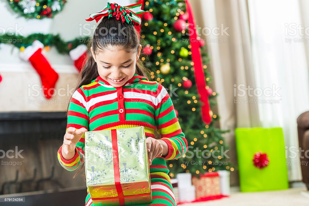 Happy girl on Christmas morning opening up her gifts stock photo