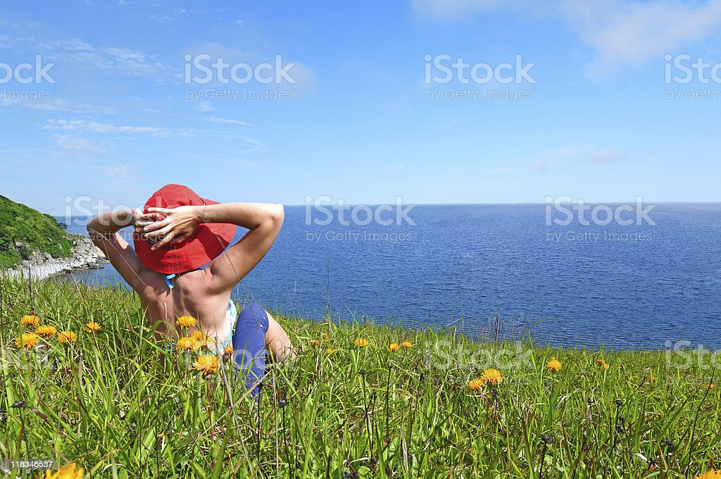 happy girl on the flower meadow against sea landscape stock photo