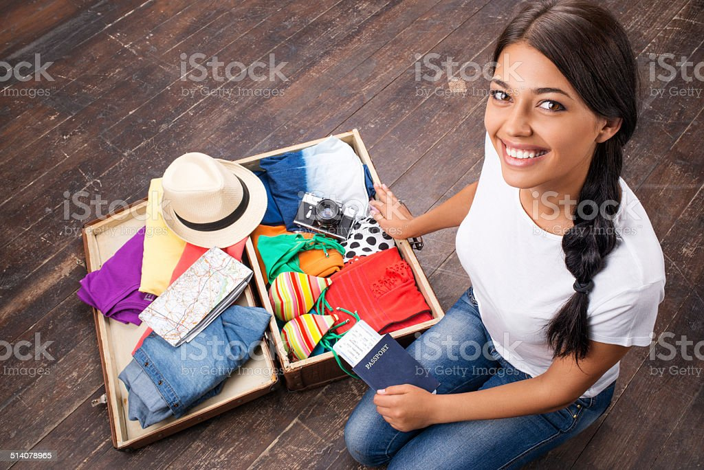 Happy girl packing her suitcase stock photo