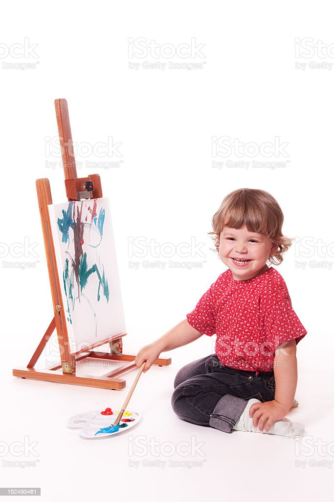 Happy girl painting on easel stock photo