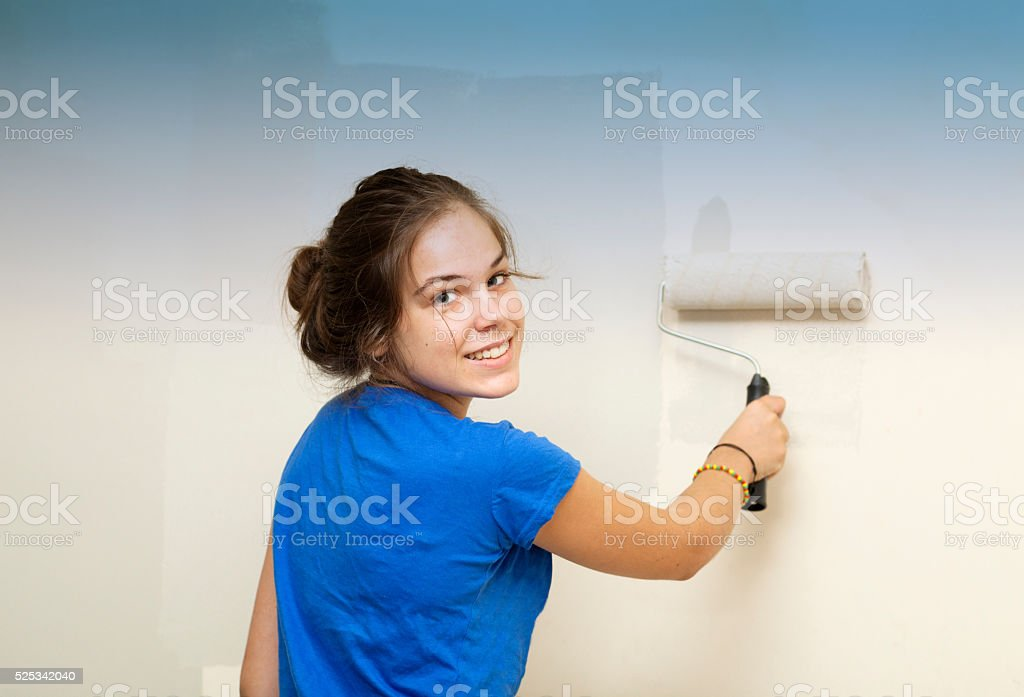Happy Girl painting the wall of the room stock photo