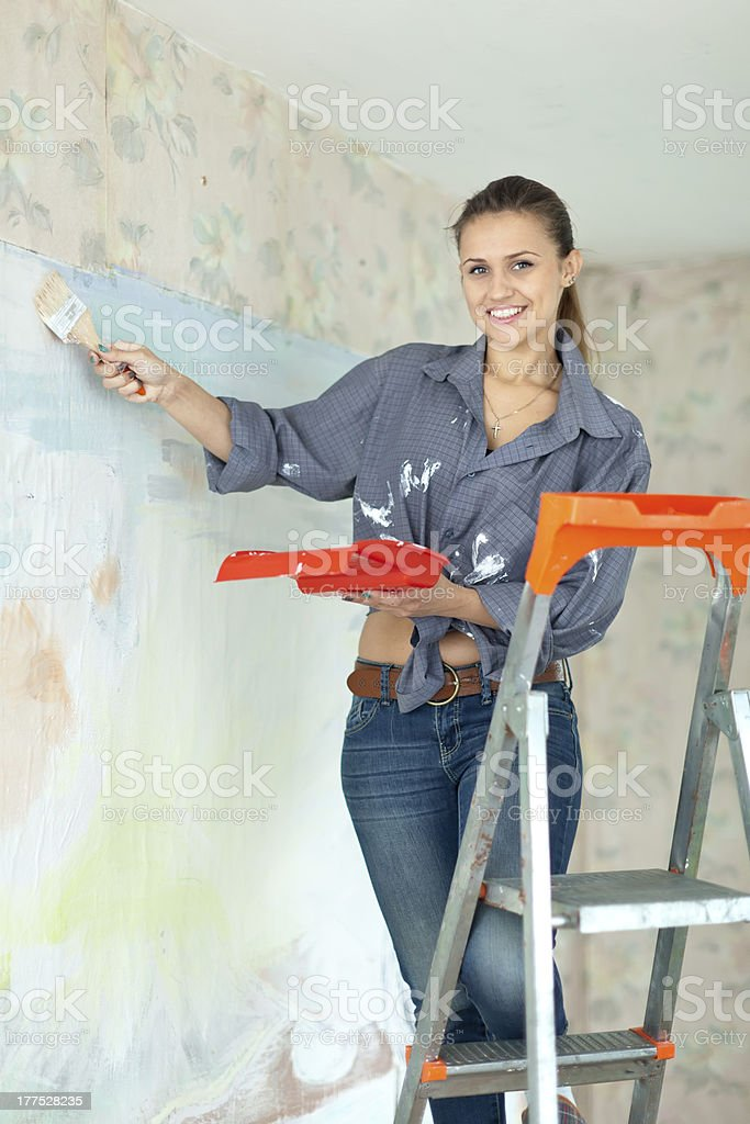 Happy girl paints wall with brush royalty-free stock photo
